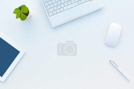 Photo for Asymmetrical Business Composition on White Office Desk with Flower Computer Laptop Cropped Tablet PC Mouse and Pen - Royalty Free Image
