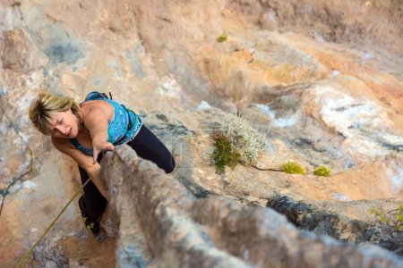 Blond Cute Climber on rocky terrain makes difficult move