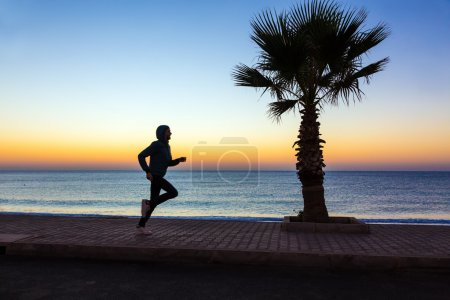 Man jogging on seafront alley with Palm Tree along calm Sea colorful sunrise