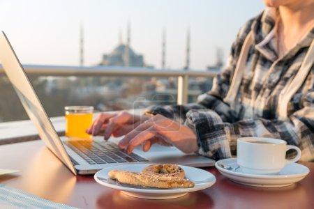 Photo pour Travail de personne petit déjeuner de travail sur ordinateur portable à la terrasse du café sur la Table avec la tasse à café de jus d'Orange et de boulangerie gâteau asiatique paysage urbain sur fond - image libre de droit