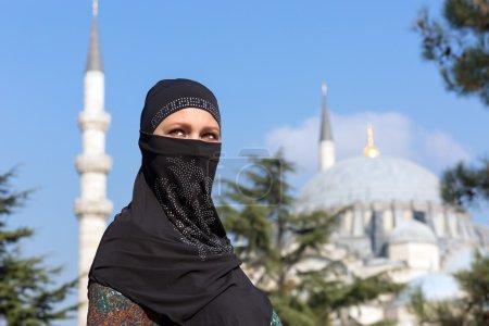 Photo pour Portrait de la belle femme arabe dans les vêtements musulmans traditionnels Moyen-Orient Paysage urbain avec mosquée et minarets sur fond - image libre de droit