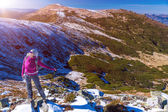 Female Hiker standing on snowy Rocks admiring scenic Winter Mountain View Sun