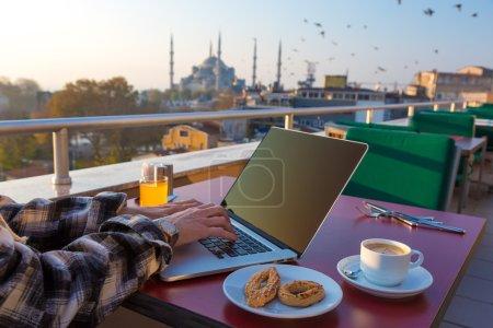 Photo pour Travail petit déjeuner personne travaillant sur ordinateur portable à la terrasse du café sur la Table à café tasse jus d'Orange et boulangerie Cookies asiatique urbain paysage Sultan Ahmed mosquée et oiseaux qui volent sur fond - image libre de droit