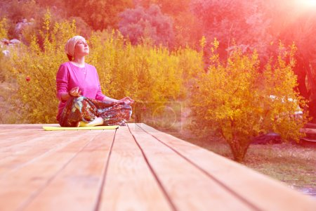 Person doing Yoga Exercise on wooden Terrace of rural Cabin