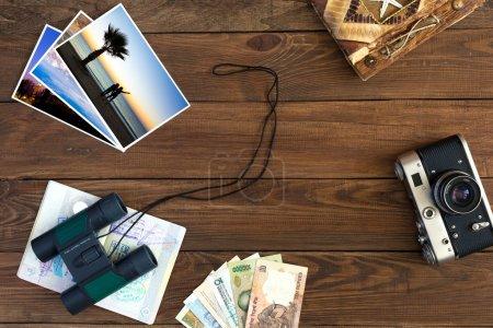 Foto de Viajes recuerdos Vintage composición con vieja cámara exóticas notas de la moneda de países hecha a mano viaje libro binoculares y pasaporte abierto con muchos sellos de entrada visas fotos a Color sobre fondo de madera - Imagen libre de derechos