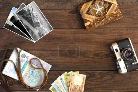 Foto de Viajes recuerdos Vintage composición con viejo cámara exóticas notas de países de la moneda a mano libro de viajes y pasaporte abierto con muchas visas y entrada de estampillas Tarjetas fotográficas sobre fondo de madera - Imagen libre de derechos