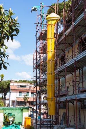 Photo pour Tube en plastique utilisé dans la construction pour déverser des débris montés sur un échafaudage - image libre de droit