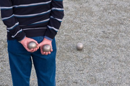 Man holding two balls behind his back playing petanque