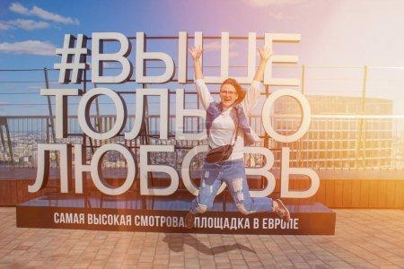 """Photo pour Inscription en russe """"Au-dessus de l'amour seulement"""". Une jeune femme heureuse portant un jean saute les mains en l'air. Le plus haut pont d'observation d'Europe. Fille a sauté sur le texte de fond sur l'amour en Russie, Moscou. - image libre de droit"""