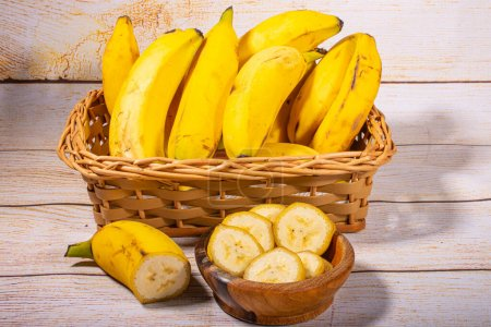 Photo for Banana cut into slices in a wooden bowl in the highlight and in the background bananas in a wicker basket on a light wooden background. - Royalty Free Image