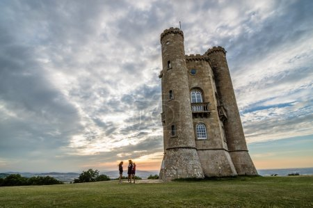 Photo for Broadway, UK - August 12, 2015:  Broadway Tower with the silhouettes of tourists at sunset. It was constructed in 18th Century. - Royalty Free Image