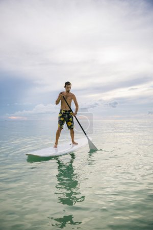Man stand up on paddle board at sunset