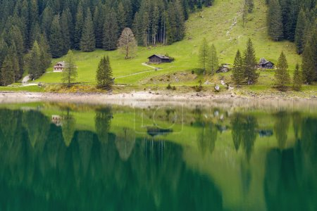 Alpine  mountain house in the forest reflected in water