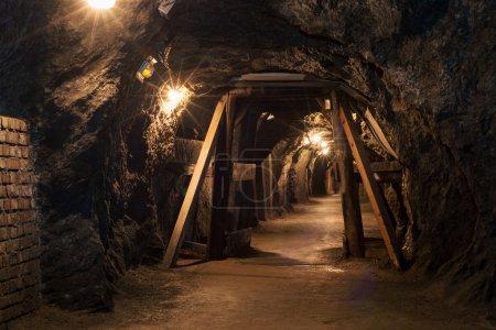 Photo pour Long tunnel éclairci à travers la mine de gypse avec des poutres en bois - image libre de droit