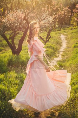 Attractive woman in pink dress enjoying the nature