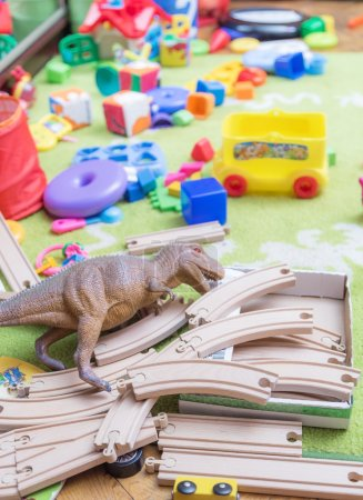 Photo for Childrens toys scattered in disarray on the carpet. - Royalty Free Image