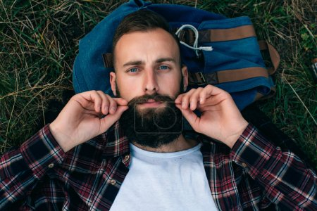 Photo for Bearded man lying on the grass relax and dream, lifestyle concept - Royalty Free Image