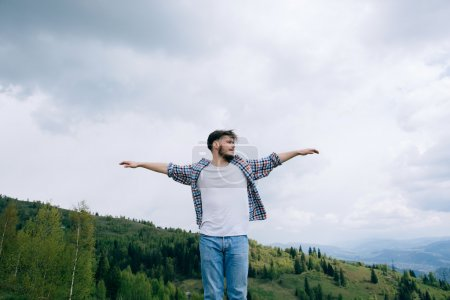 Photo pour Homme barbu leva les bras vers le haut dans les montagnes, la liberté - image libre de droit