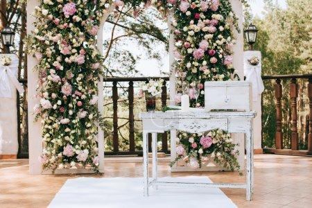 Photo pour Arc pour la cérémonie de mariage, décoré de fleurs fraîches dans une pinède - image libre de droit