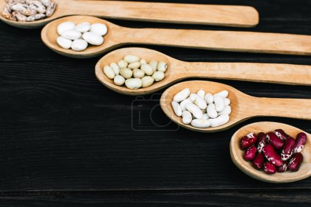 A colorful of beans in wood spoon on wood background