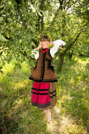 young girl, Ukrainian national costume, standing barefoot on the