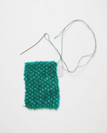 Woven beaded mesh and needle