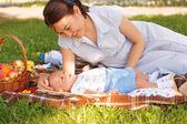 Roztomilý malý chlapeček s matkou na piknik v parku léta
