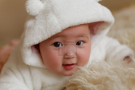 Beautiful cute baby girl with bow on the fur ground