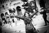 Beautiful and happy kazakh woman playing with doves