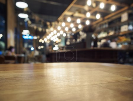 Photo pour Top of Wooden Table with Blurred Bar Interior restaurant Background - image libre de droit