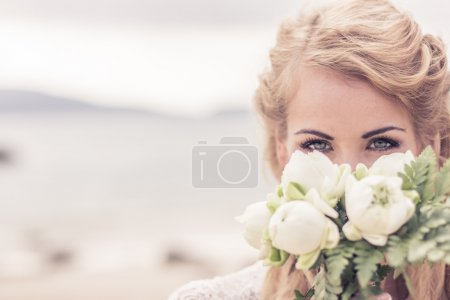 Happy beautiful girl in a wedding dress with a bouquet by the sea