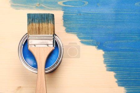 Foto de Pintura pincel en la lata acostado sobre fondo de madera. La superficie es mitad tonificada con color azul - Imagen libre de derechos