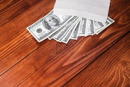 Photo pour Dollars dans une enveloppe couchée sur un fond en bois avec place pour le texte - image libre de droit
