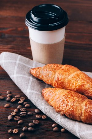 Photo for Coffee to go with croissants or baking lying on wooden table - Royalty Free Image