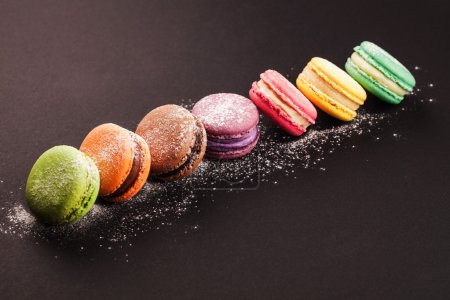 Photo for Row of french colorful macaroons with powdered sugar, lying on black background - Royalty Free Image