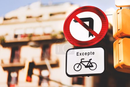 Photo pour Close-up of No left turn except bicycles signs in Barcelona against a blurred background of the building and the blue sky - image libre de droit