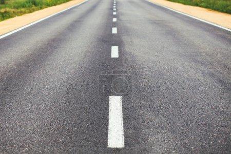 Photo pour Blanc en ligne sur la surface de la route avec le bord de la route de démarcation - image libre de droit
