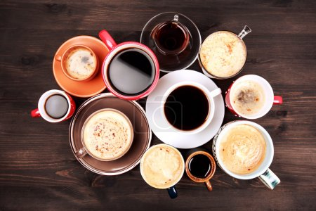 Photo for Many different cups of coffee on dark wooden table, top view - Royalty Free Image