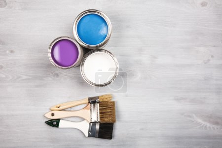 Paint cans and colored brushes on white background
