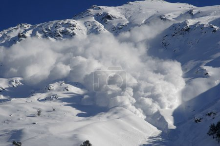 Dry snow avalanche with a powder cloud close to the village Terskol, Elbrus region.