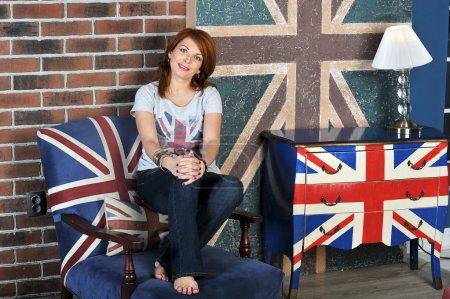 Photo pour Jeune fille assise sur la table de chevet sur le fond de drapeau anglais - image libre de droit