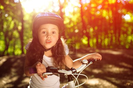 little girl with bicycle in summer park against sunset
