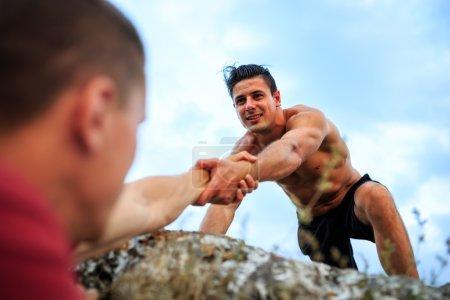 Photo pour Un homme aide quelqu'un à escalader le rocher - image libre de droit