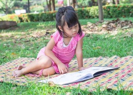 Photo pour Portrait extérieur d'une jolie petite fille lisant un livre - image libre de droit