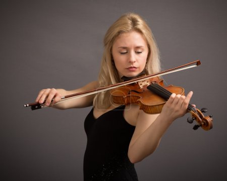 Photo for Studio portrait of a beautiful young blond female violin player playing a lovely tune isolated against a dark grey background. - Royalty Free Image