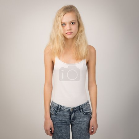Blond Serious Girl Standing Straight Wearing A White Top