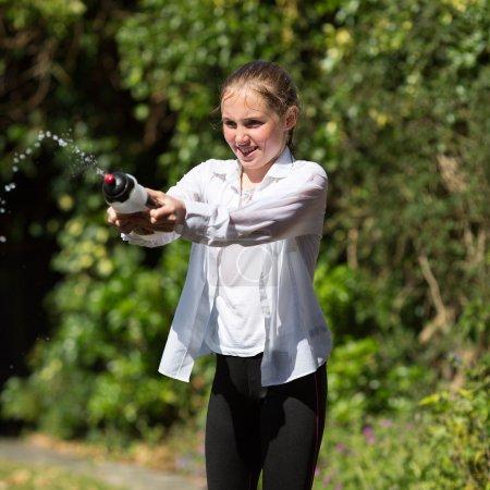 humide adolescent fille gicle eau à partir de bouteille