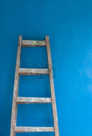Lladder against blue wall