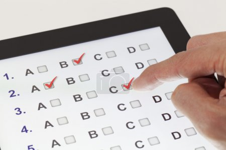 Photo for Finger clicking on a tablet with multiple-choice questions - Royalty Free Image