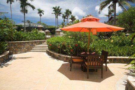 Photo pour Chaises en plein air sous le soleil dans une station balnéaire tropicale - image libre de droit